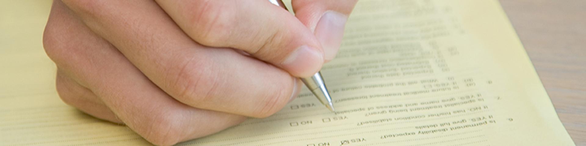 Formular-Center der BBBank: Hand eines Kunden füllt Formulare aus.