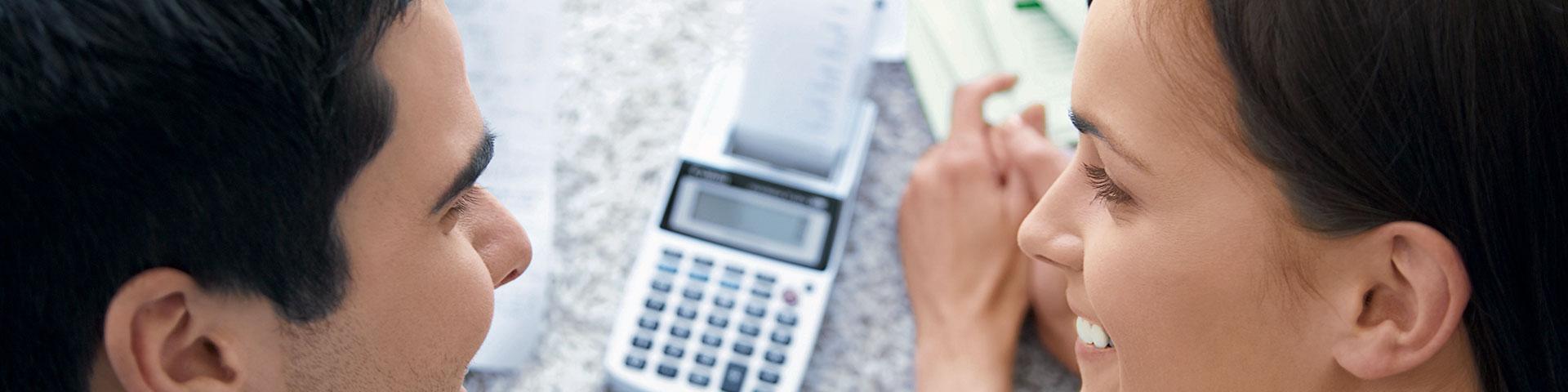 Preise und Konditionen: Paar rechnet mit Hilfe des Preis- und Konditionsverzeichnis der BBBank ihre Vorteile aus.
