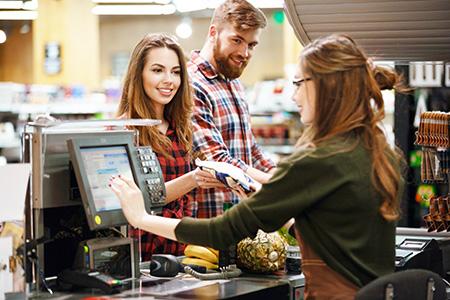 BankCard wird per Hand in einen der über 395.000 bundesweiten BBBank Geldautomaten für kostenfreies Geldabheben eingeführt.