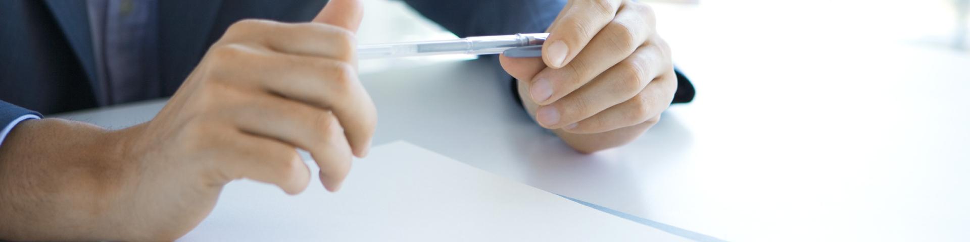 Mann mit Kulli in der Hand macht sich Gedanken über die Satzung sowie den Geschäfts- und Offenlegungsbericht