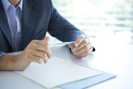 BBBank Geschäftsberichte: Hände aufgelehnt auf einen Schreibtisch halten einen Kugelschreiber. Dies ist ein Symbol für die niedergeschriebenen Geschäftsberichte.